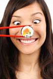 Funny sushi woman. Funny picture of woman with salmon maki sushi stock photography