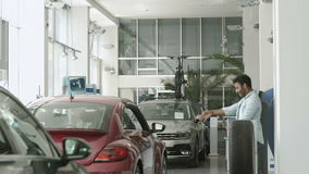Funny swarthy guy dancing near the car in car showroom. Handsome swarthy guy stands near the car. Funny man suddenly start dancing and moves backward. Happy girl stock video footage