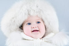 Funny sweet baby girl wearing a big fur hat Royalty Free Stock Photography