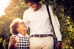 Funny talk about school. African American father and his daughter walking trough city park stock photos