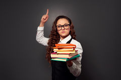 Funny teacher in glasses with pile of textbooks. Picture over dark background royalty free stock images