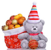 Funny teddy bear in hat with santa claus bag full of toys Royalty Free Stock Image