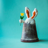 Funny teddy rabbit with tulip sitting in a broken flower pot. Royalty Free Stock Image
