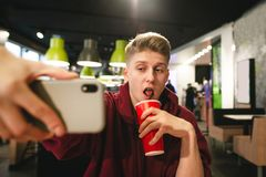 Funny teen drinks a cola from a red glass and poses a smartphone camera on the background of the cafe royalty free stock photo
