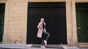 Funny teen girl dancing in a down jacket against the background of a garage in the city. Street, people, ordinary day