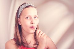 Funny teen girl eating lollypop Stock Photos