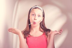 Funny teen girl eating lollypop Royalty Free Stock Photos