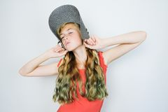 Caucasian girl in hat and red dress posing on grey background. Funny teen girl with  green dyed curly long hair. Millennial generation concept royalty free stock image