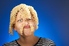 Funny teen girl with macaroni instead hair Stock Photos