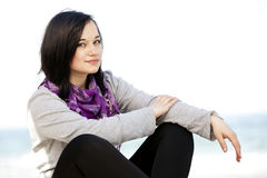 Funny teen girl sitting near the sea. Royalty Free Stock Photography