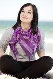 Funny teen girl sitting on the sand at the beach. Royalty Free Stock Photo