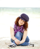 Funny teen girl sitting on the sand at the beach. Royalty Free Stock Photography