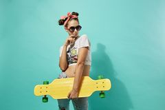 Funny teen girl in sunglasses and pink bow on her head dressed in jeans and top stands with yellow skateboard on the royalty free stock photography