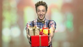 Funny teen guy giving present boxes. Male adolescent handing gift boxes on abstract blurred background. Happy winter holidays stock footage