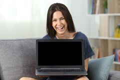 Funny teen showing a blank laptop screen at home. Fronf view portrait of a funny teen showing a blank laptop screen sitting on a couch in the living room at home royalty free stock images