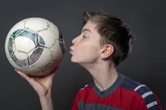 Funny teenage boy is kissing a soccer ball Royalty Free Stock Photos