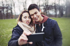 Funny teenage couple photographing themselves Stock Images