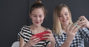 Funny teenage girls playing game on mobile phones stock video footage