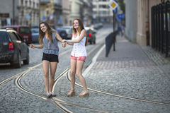 Funny teenage girls together walking on the pavement on the street. Stock Images