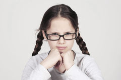 Funny teenager girl looks angry behind her spectacles Royalty Free Stock Images