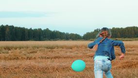 Funny teenager girl playing with balloon on wheat field in countryside. Funny teenager girl playing with balloon on wheat field on forest landscape in stock video