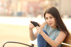Funny teenager playing games on a smart phone Stock Photography