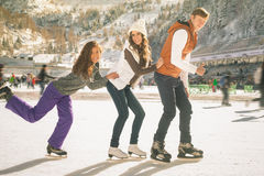 Funny teenagers girls and boy skating outdoor, ice rink Royalty Free Stock Photos