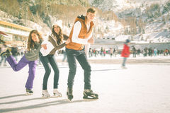 Funny teenagers girls and boy skating outdoor, ice rink stock photo