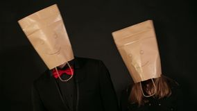 Couple with bags over heads on black background. Funny teenagers with paper bags on his head having fun on a black background, they simultaneously move their stock video