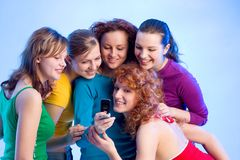 Funny text. Five beautiful girls are reading a text message on the mobilephone Stock Image