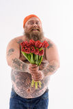 Funny thick guy giving bouquet with joy Royalty Free Stock Photo