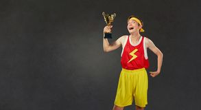 Funny thin guy in sports clothes with a championship cup in his royalty free stock photo