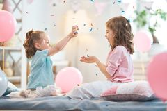 Girls are throwing confetti. Funny time. Children are playing at home. Girls are throwing confetti. Family holiday and togetherness royalty free stock images