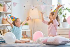 Girls are throwing confetti. Funny time. Children are playing at home. Girls are throwing confetti. Family holiday and togetherness stock image