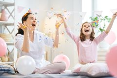 Party at home. Funny time. Mom and her child daughter are playing at home. Girls are throwing confetti. Family holiday and togetherness stock photos