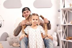 Funny time Tattoed father in a cap and his child are playing at home. Dad is doing his daughter`s hair in her bedroom. They are looking at the camera and royalty free stock images