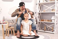 Funny time Tattoed father in a cap and his child are playing at home. Dad is doing his daughter`s hair in her bedroom. Funny time Tattoed father in a cap and his royalty free stock photo