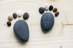 Funny tiny stone feet and ten toes on wooden background, stone in the shape of a human feet. Two tiny stone feet and ten toes on wooden background, stone in the Stock Images