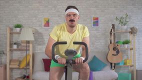 Funny tired athlete from the 80`s with a mustache engaged at home on a exercise bike slow mo. Funny tired man athlete from the 80`s with a mustache engaged at stock video