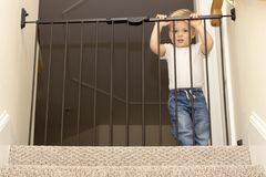 Funny toddler approaching safety gate of stairs.  Royalty Free Stock Photos