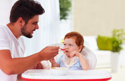 Funny toddler baby looking suspiciously on father during a meal Stock Photo