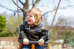 Funny toddler boy having fun on swing Royalty Free Stock Images