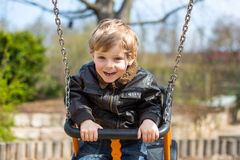 Funny toddler boy having fun on swing Royalty Free Stock Image