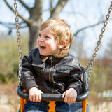 Funny toddler boy having fun on swing Royalty Free Stock Photography