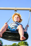 Funny toddler boy having fun on swing Stock Photo
