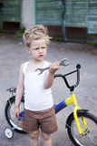Funny toddler boy repairing his broken bike. Childhood.Cycling Stock Photo