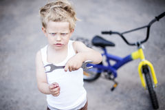Funny toddler boy repairing his broken bike. Childhood.Cycling Royalty Free Stock Images