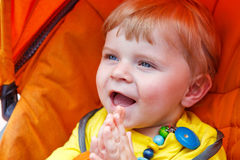 Funny toddler boy smiling outdoor in orange stroller Royalty Free Stock Photos