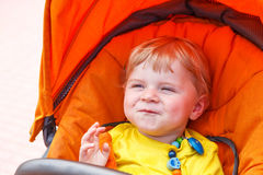 Funny toddler boy smiling outdoor in orange stroller Stock Photo