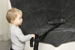 Funny toddler cleaning up the sofa with vacuum cleaner royalty free stock images